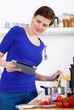 Frau, die Teigwarenteller vorbereitet und das Rezept auf einer Tablette überprüft Lizenzfreie Stockfotografie