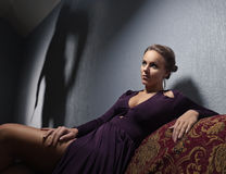 Junge Frau im Abendkleid und im Angeklagter ` s Schatten lizenzfreies stockfoto
