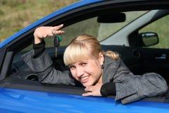 Junge Frau im Auto mit Taste Stockbild