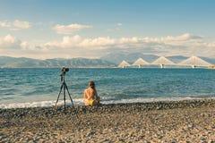 Junge Frau im Badeanzug auf dem Strand mit Stativ und Kamera auf Rion-Antirion überbrücken Hintergrund nahe Patras, Griechenland Lizenzfreies Stockbild