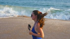 Junge Frau im Badeanzug, der auf Seestrand und hörender Musik läuft Mädchen, das entlang Ozeanufer rüttelt Weiblicher Sportler stock video