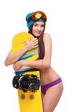 Junge Frau im Badeanzug, der Snowboard umarmt Stockfoto