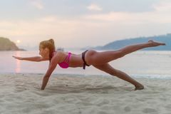 Junge Frau im Badeanzug trainierend auf dem Strand, der ihre Beine während des Sonnenuntergangs in Meer ausdehnt Eignungsmädchen, stockfotografie