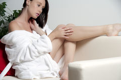 Junge Frau im Bademantel auf Sofa Stockfotografie