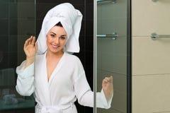 Junge Frau im Bademantel im Hotelbadezimmer Stockbild