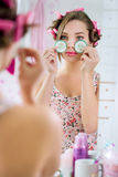 Junge Frau im Bademantel mit Gurke auf Augen Stockfoto