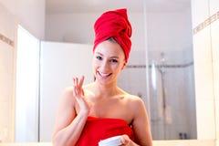 Junge Frau im Badezimmer untersucht einen Spiegel lizenzfreie stockfotos