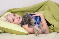 Junge Frau im Bett, das mit Schnauzerhund spielt Stockfotografie