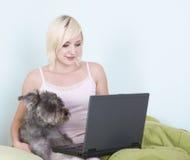 Junge Frau im Bett mit Laptop- und Schnauzerhund Lizenzfreies Stockbild