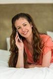 Junge Frau im Bett sprechend am Handy Stockfotografie