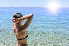 Junge Frau im Bikini auf dem blauen Seeufer Lizenzfreies Stockbild