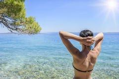 Junge Frau im Bikini auf dem blauen Seeufer Lizenzfreie Stockfotografie