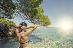 Junge Frau im Bikini auf dem blauen Seeufer Stockbilder