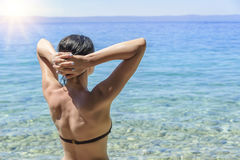 Junge Frau im Bikini auf dem blauen Seeufer Lizenzfreies Stockfoto