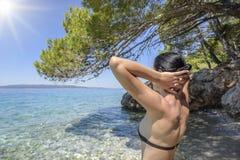 Junge Frau im Bikini auf dem blauen Seeufer Lizenzfreie Stockbilder