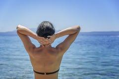 Junge Frau im Bikini auf dem blauen Seeufer Stockfotos
