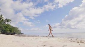 Junge Frau im Bikini auf nass Sand auf Seestrand auf Himmel eine Palmeansicht gehend Schönes Mädchen im Badeanzug auf Ozean stock footage
