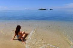 Junge Frau im Bikini, der auf einem Strand, Insel Vanua Levu, Fij sitzt stockfoto