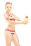Junge Frau im Bikini, der auf Sonnencreme sich setzt Stockbild