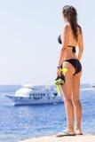 Junge Frau im Bikini, der das Schnorcheln der Ausrüstung hält Stockfoto