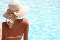 Junge Frau im Bikini, der einen Strohhut durch den Swimmingpool trägt Stockbild
