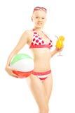 Junge Frau im Bikini, der einen Wasserball und ein Cocktail hält Stockfoto