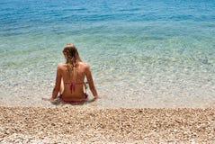 Junge Frau im Bikini, der im flachen Meer, linke Seite sitzt Stockfotos