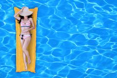 Junge Frau im Bikini, der im Swimmingpool sich entspannt lizenzfreies stockbild