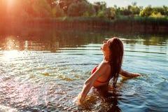 Junge Frau im Bikini, der im Wasser spielt und Spritzen macht Krasnodar Gegend, Katya lizenzfreie stockbilder