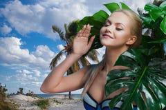 Junge Frau im blauen Bikini unter Palmen und tropischen Anlagen Stockfoto