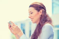 Junge Frau im blauen Hemd, das unter Verwendung des intelligenten Telefons hält Stockfoto