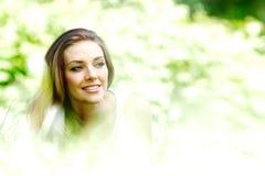 Junge Frau im blauen Kleid, das auf Gras liegt Stockfoto