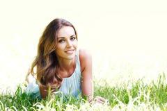 Junge Frau im blauen Kleid, das auf Gras liegt Stockfotos