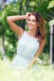 Junge Frau im blauen Kleid, das auf Gras sitzt Stockbild