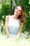 Junge Frau im blauen Kleid, das auf Gras sitzt Lizenzfreie Stockfotos