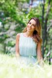 Junge Frau im blauen Kleid, das auf Gras sitzt Lizenzfreie Stockfotografie