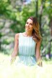Junge Frau im blauen Kleid, das auf Gras sitzt Stockfotografie