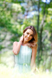 Junge Frau im blauen Kleid, das auf Gras sitzt Lizenzfreie Stockbilder