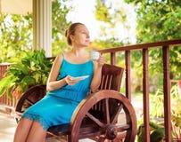Junge Frau im blauen Kleid eine Schale des Getränkes genießend stockfotos