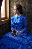 Junge Frau im blauen Weinlesekleid, das im Coupé des Retro- rai sitzt stockfotografie