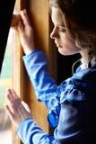 Junge Frau im blauen Weinlesekleid, das nahes Fenster im Coupé steht Stockfotografie