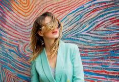 Junge Frau im Blazer der Art 90s und der Sonnenbrille lizenzfreie stockfotografie