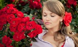 Junge Frau im Blumengarten, der rote Rosen riecht Stockfoto