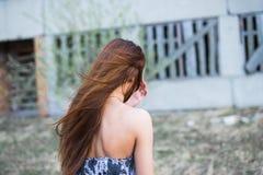 Junge Frau im Blumenkleid nahe verließ Gebäude Stockbild