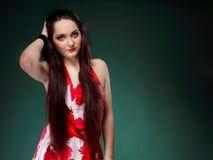 Junge Frau im blumigen Kleid des Sommers auf Grün Stockfotos
