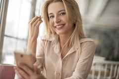 Junge Frau im Café, das die hörende Musik der Kopfhörer glücklich halten schaut Kamera sitzt Stockbild