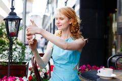 Junge Frau im Café, das Foto an ihrem Telefon macht Stockbild