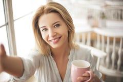 Junge Frau im Café, das mit dem Tasse Kaffee macht selfie Fotos auf glücklicher Nahaufnahme des Smartphone sitzt Stockbild