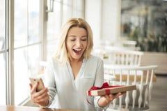 Junge Frau im Café, das Smartphone und das anwesende Lächeln halten überrascht sitzt Stockbild