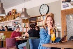 Junge Frau im Café mit dem Getränk, Tablette halten Stockfotografie